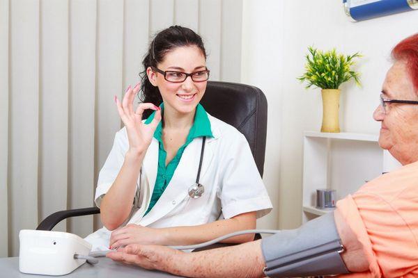 Egy orvosi rendelőben egy fehér köpenyes doktornő vérnyomást mér egy idős asszonynak, aki ok jelet mutat a kezével.