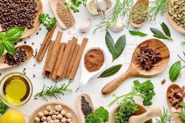 Egy asztalon sok fűszer, szegfűszeg, fahéjrudak, koriander, fekete bors, rozmaring, petrezselyem, babérlevél, fokhagyma, kapor, mogyoró, citrom.