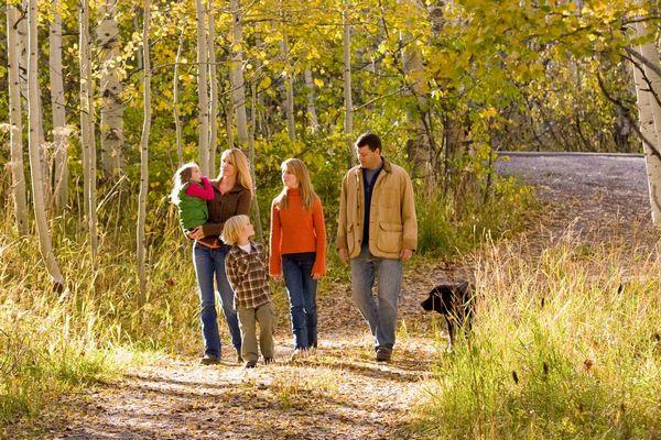 Egy őszi erdőben egy család kutyájukkal sétál, anya, apa és három gyerekük.