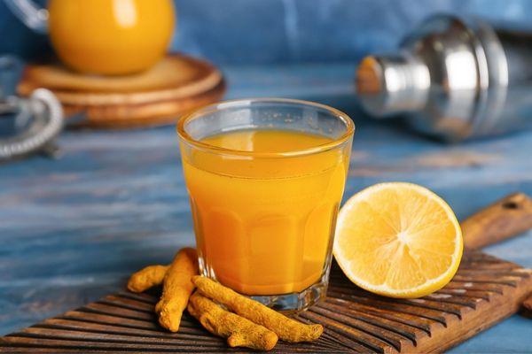Egy asztalon egy üveg pohárban kurkumatea, mellette kurkuma és félbe vágott narancs.