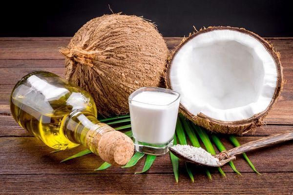 Egy asztalon félbe vágott kókuszdió, mellettük pohárban kókusztej, és kanálban kókuszreszelék és üvegben kókuszolaj.