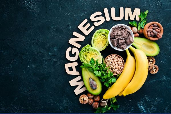 Egy sötét szürke asztalom magnézium felirat, mellette magnéziumot tartalmazó élelmiszerek, banánok, avokádó, kakaóbab, dió, étcsokoládé, mogyoró, csicseriborsó, petrezselyemzöld.
