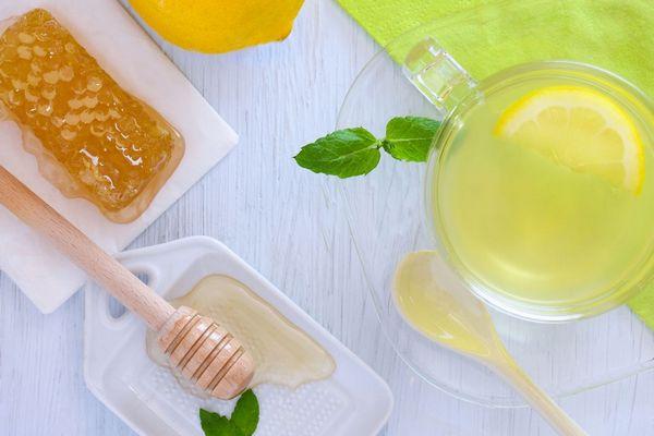 Egy asztalon lépesméz, citrom, egy üvegpohárban mézes citromos víz.