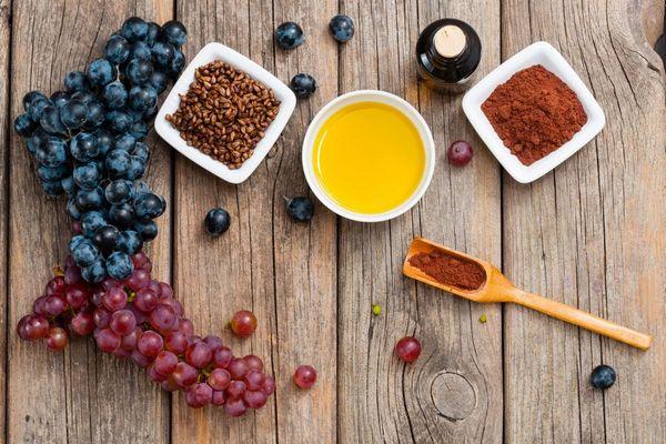 Egy asztalon szőlőfürtök, mellettük szőlőmagok, szőlőmagörlemény és szőlőmag-kivonat egy kis tálban.