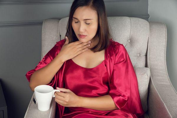 Egy szürke fotelben bíbor színű köntösben fiatal nő ül, kezével a fájós torkát fogja, miközben teát iszik.