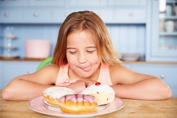 Egy asztalnál egy kislány nyelvével a száját nyalja, előtte tányéron három cukros fánk.