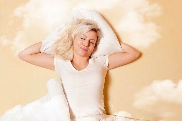 Egy krém színű ágyon fiatal szőke hajó lány fekszik csukott szemmel, álmában mosolyog.