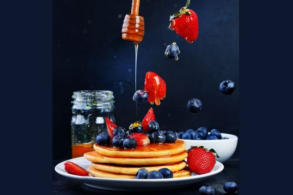 Egy sötét kék háttér előtt egy tányéron palacsinták egymásra pakolva, mellette mézes üveg, a palacsintákra méz csöpög, eper és fekete áfonya körülötte és felette. mellette egy tálban fekete áfonyák.