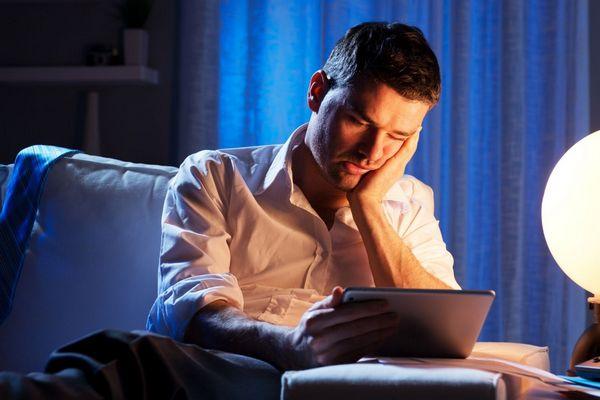 Éjszaka lámpa mellett tabletjén dolgozik egy férfi, fáradt fejét kezével tartja.