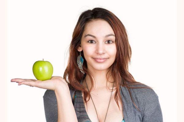 Egy fiatal lány mosolyog, jobb tenyerében egy zöld almát tart.