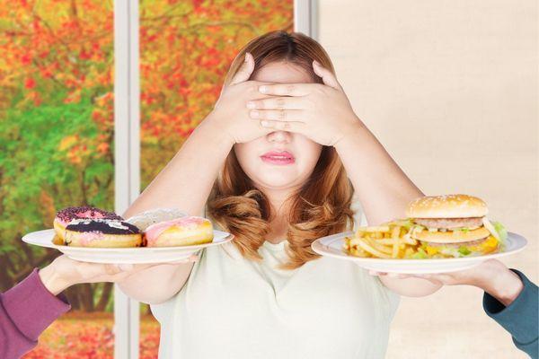 Egy elhízott nő két kezével eltakarja a szemét, hogy ne lással azt a két tányért, melyekben fánkokat, hambugert és sült krumplit kínálnak fel neki.