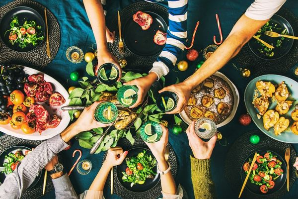 Vacsora közben terített asztal mellett ülve emberek koccintanak egymással.