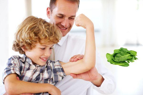Egy kisfiú a bicepszét mutatja az apukájának, mellettük spenótlevelek.