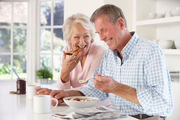 Egy nyugdíjas házaspár a konyhájukban reggelizik, a férfi müzlit, a felesége pirítós kenyeret eszik.