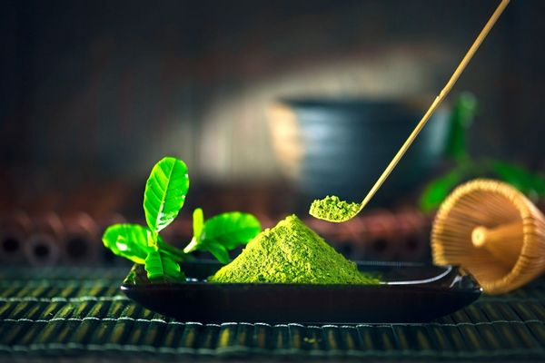 Egy asztalon matcha tea levelei, mellette egy fekete tálban matcha tea, amelyből kanállal kivesznek.