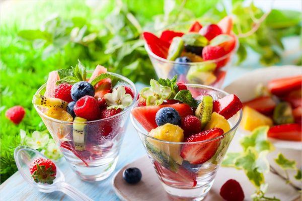 Egy asztalon három üvegpohárban sok gyümölcs, eper, fekete áfonya, kivi, dinnye.
